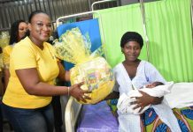 Mrs Jemima Kotei Walsh, Customer Relations Executive of MTN Ghana presenting hamper to a mother