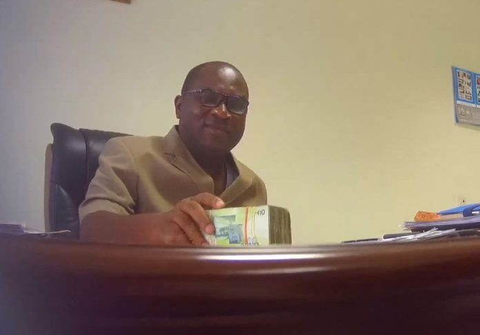 Robert Sarfo-Mensah in the act of taking the cash in his office